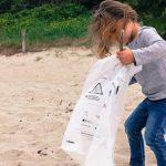 une petite fille collecte des déchets sur une plage en Bretagne