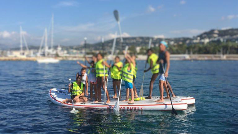 Enfants sur paddle géant collecte de déchets Cannes